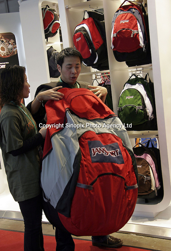 Visitors have fun with an oversized backpack at the ISPO China 2005 (International Trade Show for Sports, Fashion, and Lifestyle Brands) in Shanghai, China. Many of the world's leading sports equipment makers are rushing into China as the country is expected to become one of the top three markets in the world for sporting goods by 2008..16-MAR-05