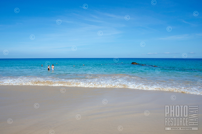 Couple about to snorkel at Hapuna Beach, along the Big Island of Hawai'i's Kohala Coast. This white sand beach has been rated one of the best beaches in the world time and time again.