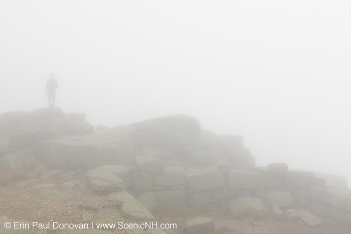 A hiker on the Appalachian Trail (Franconia Ridge Trail) on the summit of Mount Lafayette in the White Mountains, New Hampshire USA in foggy conditions during the autumn months.
