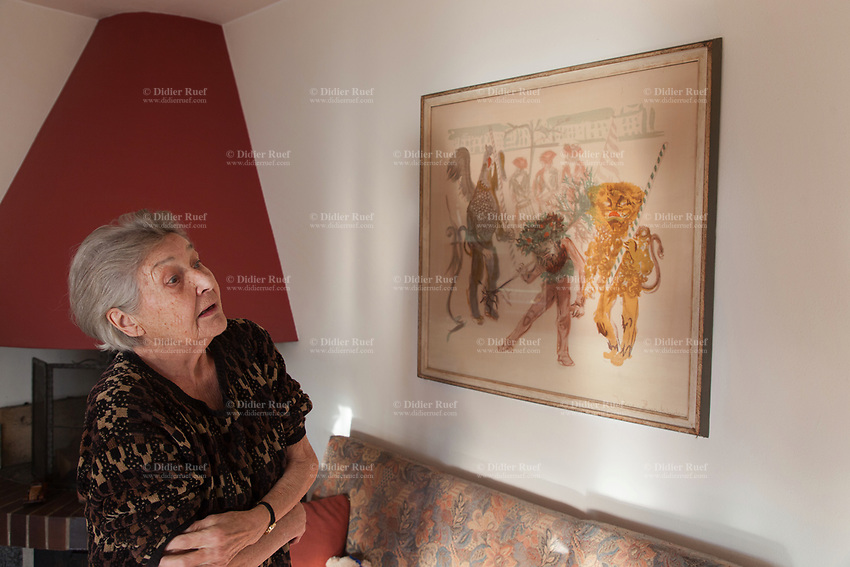 Switzerland. Canton Ticino. Sala. Elsy (Elsa) Hofer Ferrari Ramuz is 86 years old. She stands in her living room and looks at a painting by the artist Irène Zurkinden on the Basel Carnival. Elsy Hofer Ferrari Ramuz is the niece of Charles-Ferdinand Ramuz (September 24, 1878 – May 23, 1947) who was a French-speaking Swiss writer. 14.11.2017 © 2017 Didier Ruef