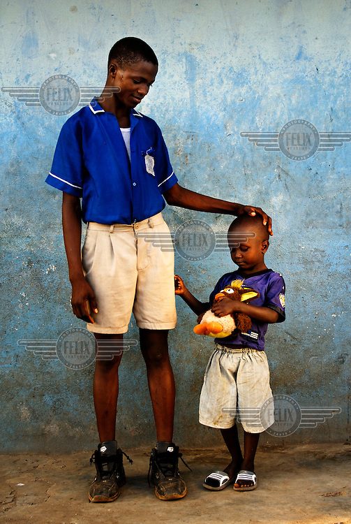 12 year old Ibrahim Kamara helps to take care of his three year old cousin Ibrahim Tarawallie, after his mother died in childbirth. Sierra Leone has the highest maternal mortality rate in the world, with one in every eight women dying in childbirth.....