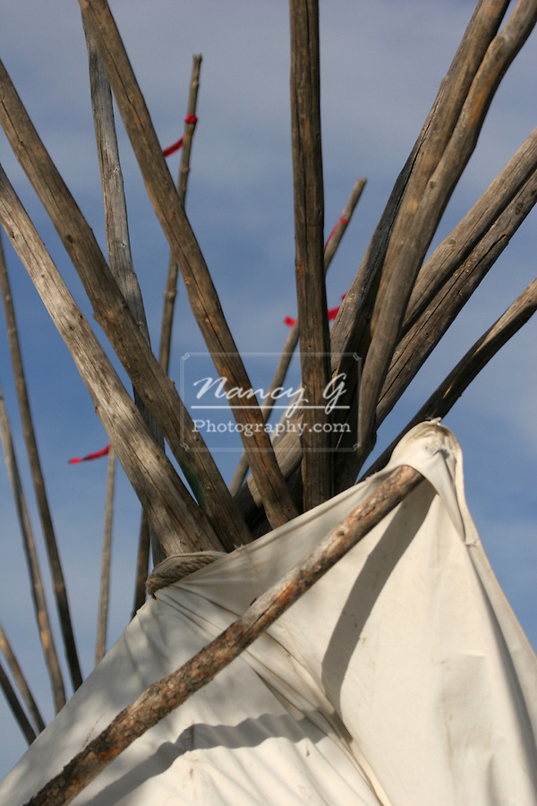 The wood supports with red ties on two tipis in a Native American Sioux Indian village in South Dakota