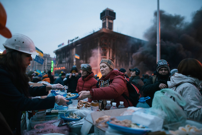 A women gets food in a improvised mensa near the barricades. The occupation of Indipendence Square (Maidan Nezalezhnosti) continues. The police attacked during yesterday afternoon and at least 26 peoples died. President Yanukovich today tagged the occupiers as terrorist and the square is preparing for a major intervention by the police during the night. People who were living in, now burned, tents and building have been partially relocated to St. Michael Church which act also as a coordination for the firs aid. People have destroyed the cobblestone to make stones to thrown and built molotov cocktails to resist the comng night.