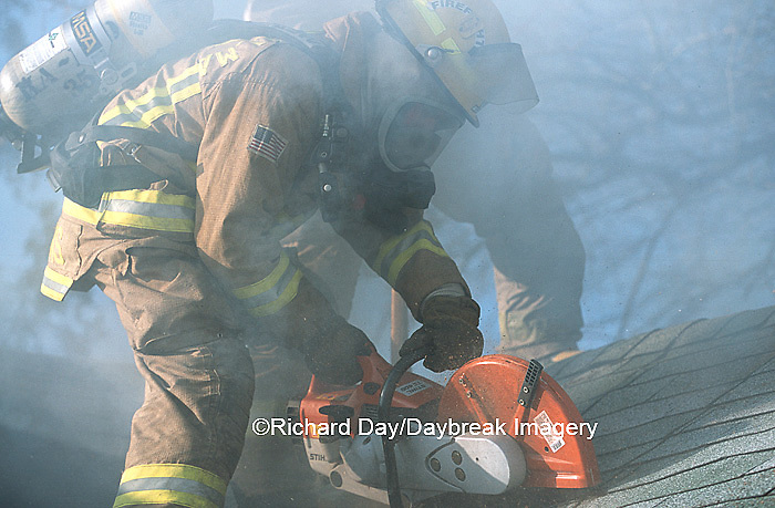 63818-01615 Firefighter using saw to ventilate smoke from house fire  Kinmundy-Alma Fire District,  Kinmundy IL