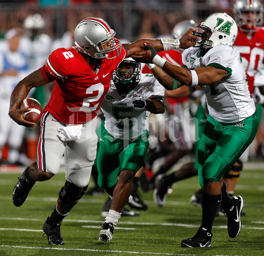 Ohio State quarterback Terrelle Pryor (2) stiff arms Marshall defensive tackle Demetrius Thompson (77) during the third quarter of the NCAA football game at Ohio Stadium on Thursday, September 2, 2010. (Photo by Jonathan Quilter)