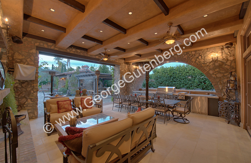 Large table and seating area is seen in outdoor living area under cover