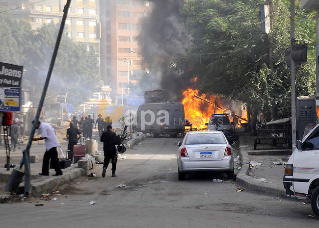 Egyptians walk past a burning police car in front of al-Zamalek football club's headquarters in Cairo on Sept. 19, 2013. Members of a hardcore group of fans of the Zamalek football club, the Ultra White Knights (UWK), stormed the club's headquarters in Cairo on Thursday following a protest demanding changes to the club's leadership. Photo by Ahmed Asad
