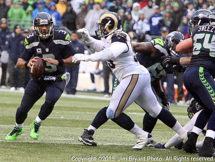 Seattle Seahawks quarterback Russell Wilson (3) looks to pass as he scrambles against the St. Louis Rams defensive tackle Aaron Donald (99) at CenturyLink Field in Seattle, Washington on December 27, 2015.  The Rams beat the Seahawks 23-17.      ©2015. Jim Bryant Photo. All Rights Reserved