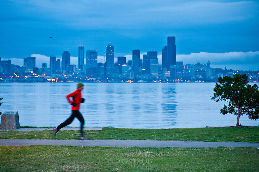 Male runner running along the West Seattle/Alki waterfront early in the morning.