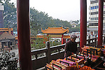 woman sells incense sticks on the porch of Buddhist temple in Guilin, China.  The pagoda roofed entrance gate, and the city, can be seen behind her
