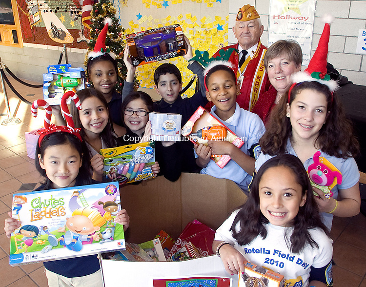 WATERBURY CT.-17 DECEMBER  2010 121610DA03-Marine Corps League Past District Commander, Raymond Carrier, back right,  gathers toys for the Toys for Tots program with the help of Meg Harrison, back left, Integrated Arts Coordinator, and Forever Wave Squad Advisor, along with members of the Forever Wave Program, clockwise from left, Fuka Asahi, Gabriel Corales, Deszren Taylor, Adriana Bird, Gabriel Corales, Coby Patterson, Samantha Plourde, and Cristina Ramos. The students and faculty donated new, unwrapped toys to be given as Christmas gifts to needy children in the community.<br /> Darlene Douty Republican American