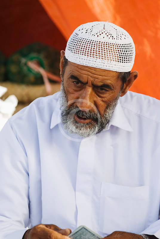 Oman, Buraimi, Arab man, seated, with traditional kummah cap