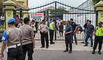 28 August 2019, Jakarta, Indonesia: - Indonesian police shut and guard the front gate at the UNHCR refugee centre in Kalideres, Jakarta. Plans to re-locate the overcrowded refugees have been fast tracked after a fight broke out between the groups, many of whom have been in Indonesia for years waiting for placement. Tensions ran high between Afghan and African groups in the centre with a lack of adequate food for the refugees being the catalyst. The African groups who were moved onto the footpath were being bussed out today. Conditions in the centre are grim and the local Indonesian population not happy with the refugees presence in the suburb.Picture by Graham Crouch/The Australian