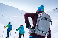 While ski touring in the Aksuu Valley, Kyrgyzstan, a woman pulls a Snickers from her backpack.