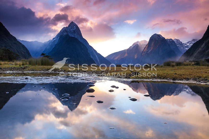 Sunset at Milford Sound - a mirror image reflection of Mitre Peak and surrounding mountains, Fiordland National Park, South Island, New Zealand - stock photo, canvas, fine art print