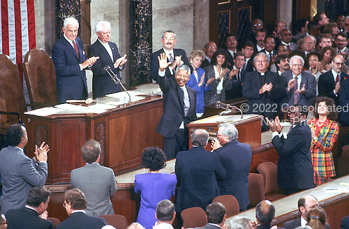 Washington, D.C. - June 26, 1990 -- Nelson Mandela, leader of the African National Congress (ANC) acknowledges the applause as he addresses a Joint Session of the United States Congress  in Washington, DC on Tuesday, June 26, 1990.  Speaker of the United States House of Representatives Tom Foley (Democrat of Washington) and United States Senator Robert Byrd (Democrat of West Virginia) applaud from left..Credit: Ron Sachs / CNP