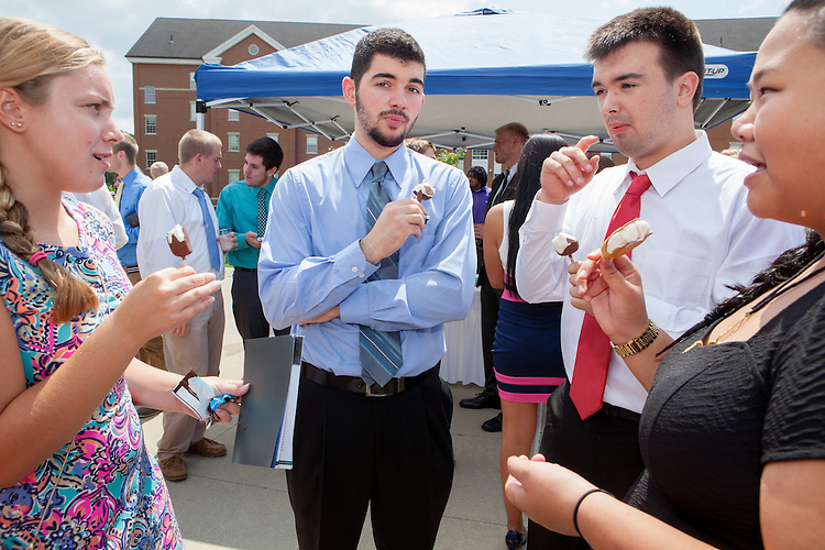 Matt Krivanek, center, and other new students to the Ohio University College of Business eat ice cream after the College of Business Freshman Convocation at Nelson Commons on Aug. 23, 2014. Photo by Lauren Pond
