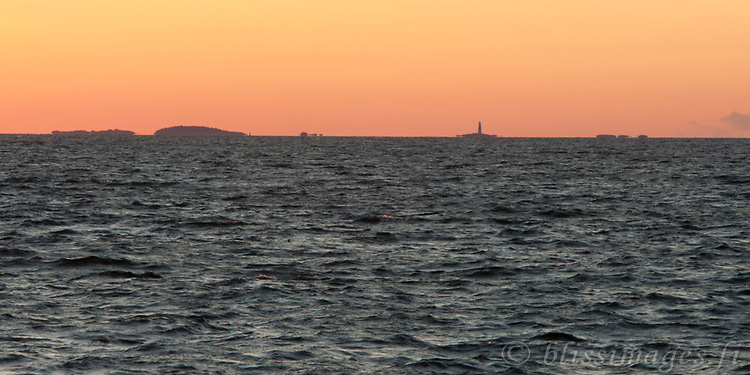 Sunrise creates mirages  at Jussarö Island and its outlying Jussarö lighthouse which stands sentinel 2.5 miles to the south on Sundharun skerry in the Gulf of Finland between Helsinki and Hanko.
