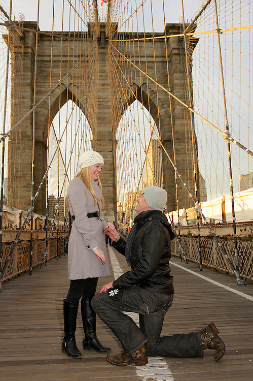Guy on his knees proposing to girlfriend on the pedestrian walkway of the Brooklyn Bridge.