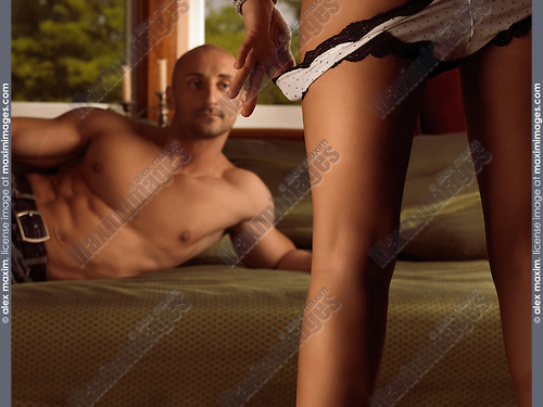 Man lying on a bed and watching a woman taking off her panties