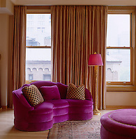 A curved pink velvet sofa in one corner of the living room against a backdrop of gold coloured curtains