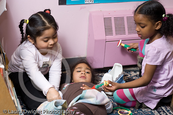 Education Preschool 3-4 year olds pretend play three girls playing  with medical kit  horizontal