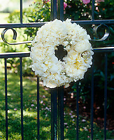 A wreath of white peonies and roses hanging on a garden gate