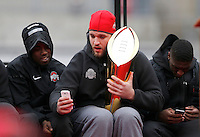 Offensive lineman Taylor Decker takes a selfie with the national championship trophy as wide receiver Corey Smith (left) watches during the Ohio State football National Championship celebration at Ohio Stadium on Saturday, January 24, 2015. (Columbus Dispatch photo by Jonathan Quilter)