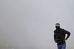 A Palestinian protester walks amid of a tear gas cloud during clashes with Israeli security forces next to the Jewish settlement of Psagot, near the West Bank city of Ramallah, November 3, 2015. The current wave of violence erupted in mid-September, fueled by rumors that Israel was trying to increase Jewish presence in Jerusalem then quickly spread across Israel, the West Bank and the Gaza Strip. Photo by Shadi Hatem