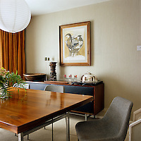 A sideboard and Hille table and chairs designed by Robin Day furnish this dining room