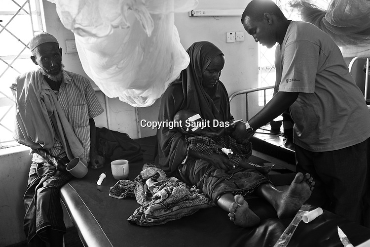 A doctor inspects a newly admitted malnutrioned child, 8 month old child Khadya Kherow who is seen with her mother, Madina Abdullahi at the stabilization ward of the GIZ Main Hospital in the Dadaab refugee camp in northeastern Kenya. Photo: Sanjit Das/Panos
