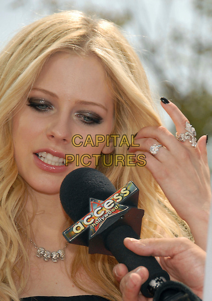 "AVRIL LAVIGNE.Red Carpet arrivals at The DreamWorks's Los Angeles Premiere of ""Over the Hedge"" held at The Mann Village Theatre in Westwood, California, USA,.April 30th 2006..portrait headshot diamante necklace rings engagement ring finger microphone access interview funny face hair black nails varnish.Ref: DVS.www.capitalpictures.com.sales@capitalpictures.com.©Debbie VanStory/Capital Pictures"