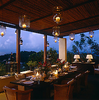 One of many terraces that surround the property is laid for dinner with glass lanterns containing candles hanging from the rattan roof covering