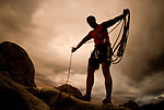A young man coils a rope while rock climbing at the City of Rocks National Reserve, Idaho.