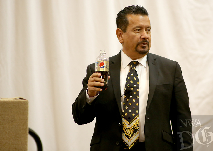 NWA Democrat-Gazette/DAVID GOTTSCHALK Richard Montanez, vice president of Multicultural Marketing at PepsiCo, displays a soda during his opening remarks Thursday, November 8, 2018, at the 2018 Northwest Arkansas Workforce Summit presented by the Springdale Chamber of Commerce at the Holiday Inn Springdale in Springdale. Montanez, the keynote speaker, was working as a janitor when he invented Frito-Lay's best-selling product Flamin' Hot Cheetos.