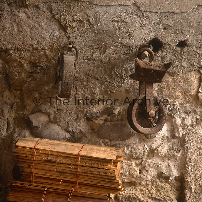 A detail of a stone wall with an iron wheel pulley and a stack of planks of wood tied with string