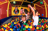 A group of young children laughing and smiling as they play in a pit of brightly colored balls.
