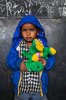 Farim, 2, poses for a portrait with a soft toy in the Guria Non-Formal Education center in the middle of the Shivdaspur red light district, Varanasi, Uttar Pradesh, India on 20 November 2013. Guria uses the soft toys as a form of therapy for the children of the women in prostitution and also use it as signals of the children's emotional wellbeing.