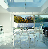 The dining table was designed by Norman Foster and has a pair of transparent armchairs by Philippe Starck with white chairs by Arne Jacobsen
