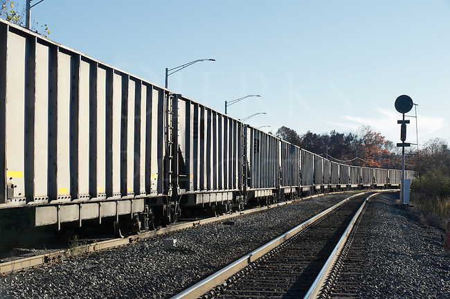 Coal train rounding a curve on a fall evening, modern gray hopper cars.