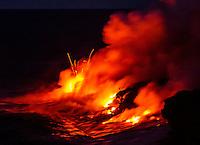 Lava explodes as it meets the sea  at night, Hawai'i Volcanoes National Park and the Kalapana border, Big Island.