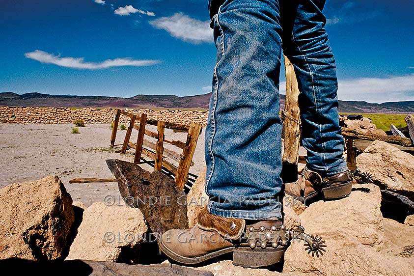 Close-up of boots and spurs, cowboy standing on rock corral. Owens Valley, California