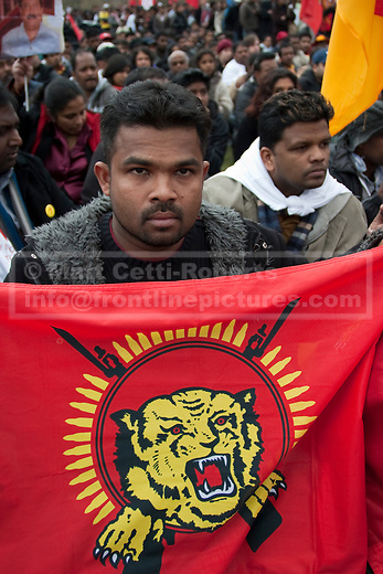 A demonstrator holds up a Tamil flag as he listens to speakers in Hyde Park.
