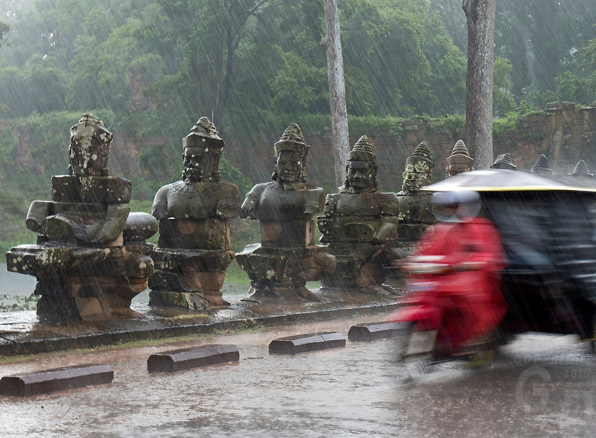 A Tuk Tuk during a heavy Monsoon rain over the stone faces at the entrance bridge and gate near Bayon Temple. Cambodia