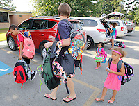 NWA Democrat-Gazette/DAVID GOTTSCHALK Lynette Washington (center) walks with her children Jeremiah, 10, (from left) Chloe, 2, Maiesha, 8, and Lydia, 4, as they carry donated backpacks filled with school supplies  into Asbell Elementary School Monday, August 3, 2015 in Fayetteville. The family is participating in The Grove Church's fourth annual Packs for Life program which collects and donates age specific school supplies. Asbell Elementary School begins today.