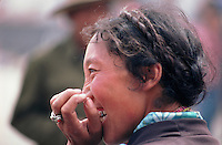 A woman in the Barghor Market of Tibet's capital, Lhasa, laughs at something that someone has said to her but, as in many Asian countries, she covers her mouth with her hand.
