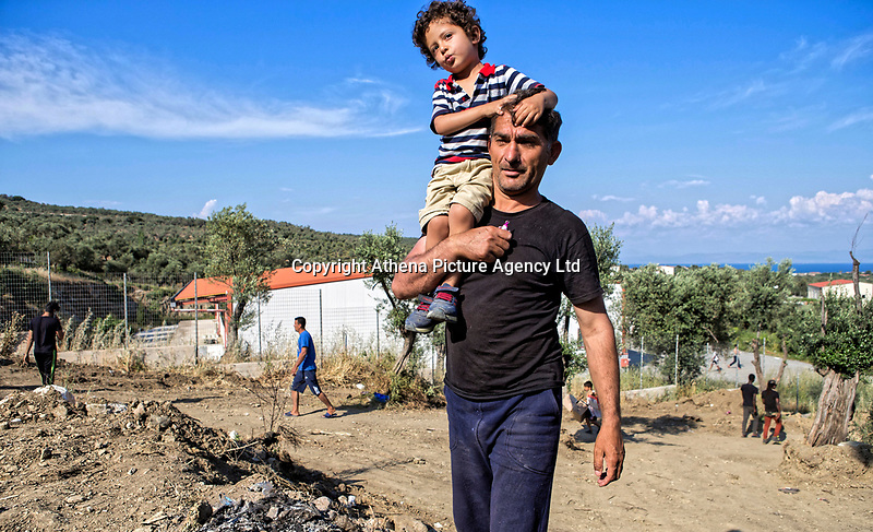 Pictured: A father carries his son on his shoulders.<br /> Re: Everyday life at the Moria refugee camp on the island of Lesbos, Greece.