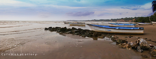 Panoramic of a calm sea and fishing boats known as pirogues beached at Erin, South Trinidad