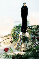 A Christmas still-life of a hand bell and a vintage black and white photograph surrounded by pine branches and rosehips
