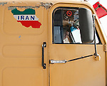 An Iranian truck driver peers from his cab as he waits at a checkpoint for his vehicle to be searched for hidden weapons at a border crossing point between Iraq and Iran.